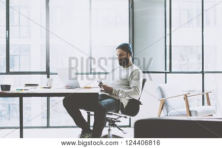 Bearded product manager working on modern open space office. Stylish man texting message smartphone. Generic design notebook wood table. Horizontal mockup.