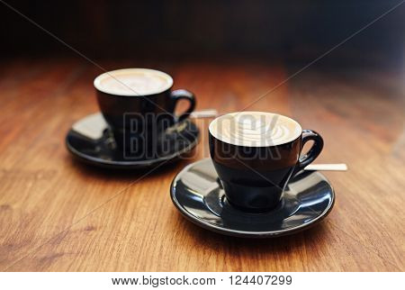 Modern black ceramic cups and saucers containing freshly made cappucinos, sitting on a wooden counter