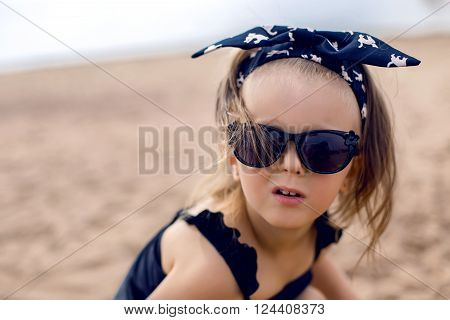a little girl stands on the shore of the beach in a black bathing suit and black glasses