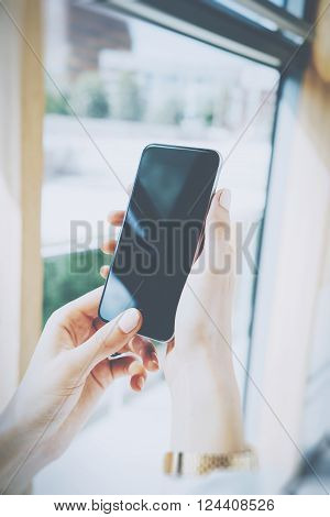 Photo woman holding modern smartphone in hands. Open space loft office. Reflection screen. Panoramic windows background. Vertical mockup.