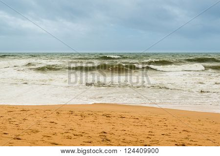 Sand beach with waves and gray-blue sky on a windy day in Albufeira, Portugal