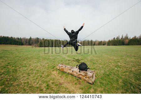 Happy young man hiker jumping on a green field over Tree trunk.Excited young hiker jumping.
