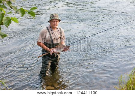 Fisherman keeps caught salmon (pink salmon) and is in the river. Far East Russia.