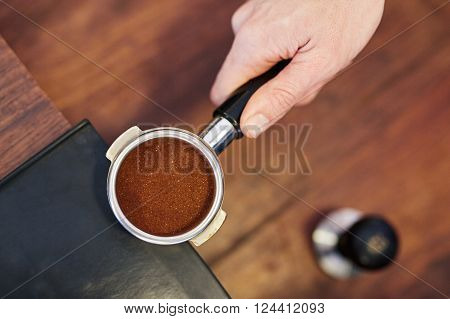Overhead shot of a person's hand holding the handle of shiny new portafilter for an espresso machine containing a perfectly level amount of fresh ground coffee, with a tamper visible on counter below