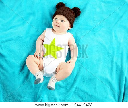 Little baby boy in knitted hat lying on the bed