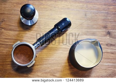 Overhead image of a stainless steel jug with milk in it, a shiny new portafilter containing fresh ground coffee and a metal tamper, all for use as accessories to a modern espresso machine