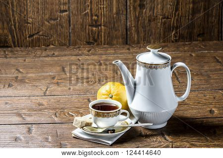 Coffee pot with coffee Cup and lemon on wooden table
