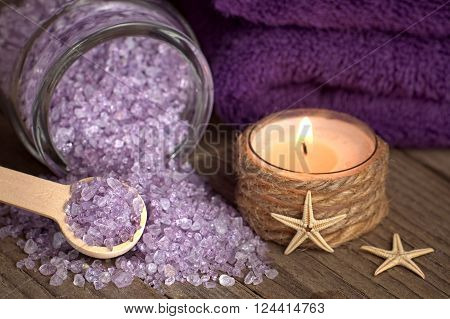 Bath salt with candle and starfishes on wood