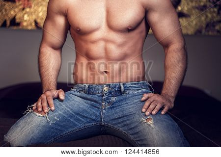Young macho sexy man body kneeling on bed in blue jeans