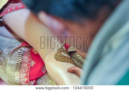 A man applying mehendi on Indian bride's hand hindu marriage rituals