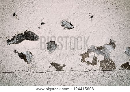 Architectural background - old detailed stone wall with cracks and spots of peeled stucco. Dark sepia tones processing