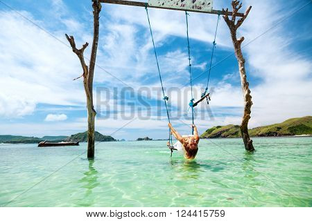 Woman swinging at tropical beach, sunny day, good weather. Swinging in paradise island.