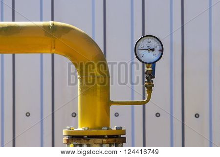 a yellow gas pipe and pressure gauge