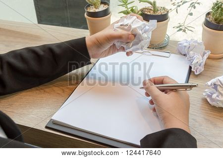 Hands of woman crumple sheets of Resume at the desk with pen mistake resume.