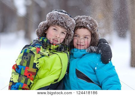 Two Cheerful Happy Boys Playing In Winter Park