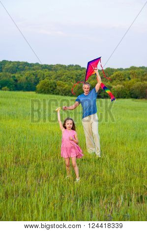 Happy dad and daughter in fild. Little girl and dad flying bright  kite.