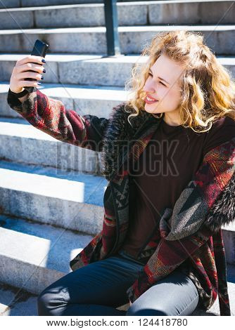 Young Hipster curly-haired woman relax in the city downtown.