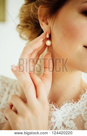 Beautiful bride with wreath of flowers in her hair in the morning puts on earring in dressing gown. Beauty model girl is wearing jewelry. Close up photo.