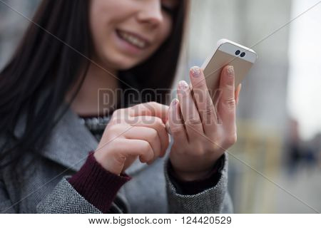 Young woman using smart phone with dual rear camera