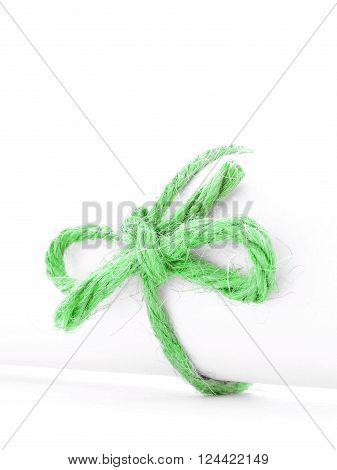 Handmade green cord knot tied on white letter tube isolated