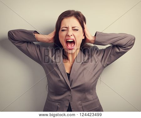 Angry Business Woman In Suit Strong Screaming With Wild Open Mouth And Holding Head The Hands. Close