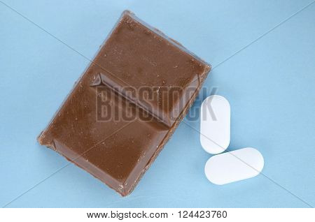 Chocolate triggers migraine headaches concept with piece of chocolate and two painkiller tablets