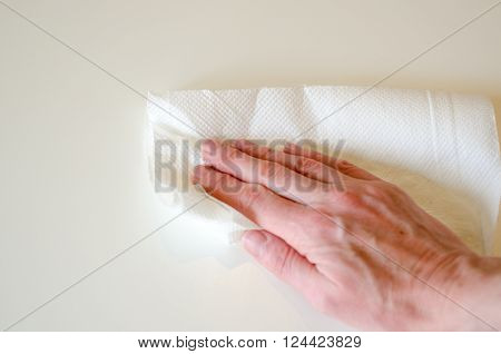 hand wiping white table with white kitchen paper