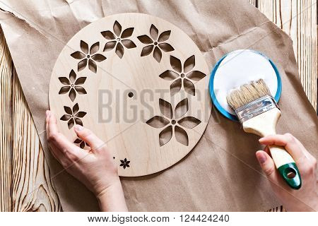 Master Class. Watch handmade. Step by step instructions for the manufacture of clocks. Hands with paint brush watch white acrylic paint. Kraft paper on a wooden background. Do it yourself