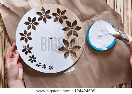 Watch handmade. Master Class. Step by step instructions for the manufacture of clocks. Hands with paint brush watch white acrylic paint. Kraft paper on a wooden background. Do it yourself