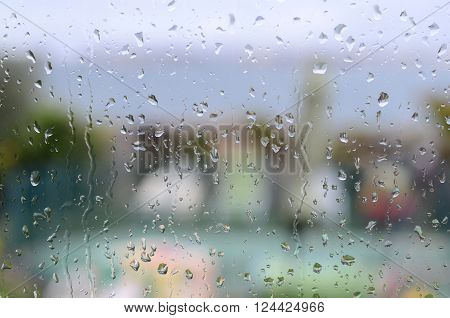 raindrops on window with garden and sea in background
