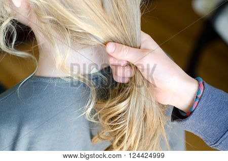 Girl getting sisters hair ready to put it into a ponytail