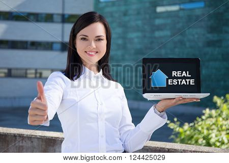 buy or rent - beautiful business woman holding laptop with real estate application