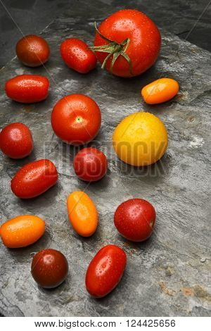 Top view of a group of medley tomatoes on a slate table.