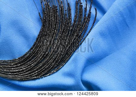 Black glass beads on blue draped silk as a background