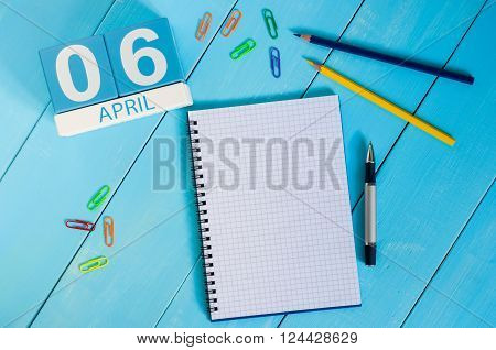 April 6th. Image of april 6 wooden color calendar on blue background.  Spring day, empty space for text.