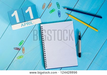 April 11th. Image of april 11 wooden color calendar on blue background.  Spring day, empty space for text. International Day of Fascist Concentration Camps Prisoners Liberation.
