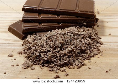 Grated chocolate and chocolate bars on wooden plank