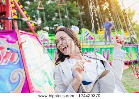 Young woman having fun at fun fair, chain swing ride, amusement park