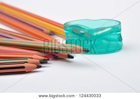 Picture Of Some Pencils With Stripes Of Different Colors And Pencil Sharpener On A White Background.