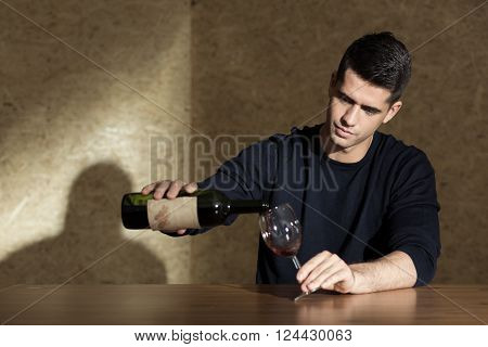 Man pouring glass of wine, sitting beside table