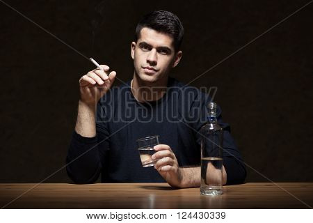 Man holding cigarette and glass, bottle of vodka on the table, dark background