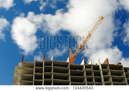Carcass of new building and crane on blue cloudy sky copyspace