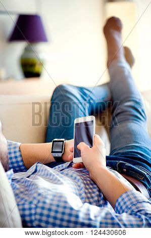Unrecognizable casual man using smart phone and smart watch, lying on the sofa in living room