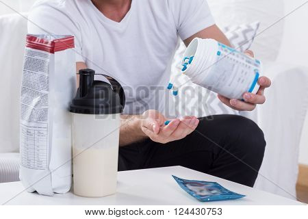 Young obsessed man taking medicine for muscles