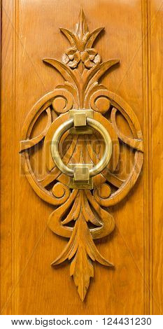 Old brass door knocker on a wooden carving placed on a front door