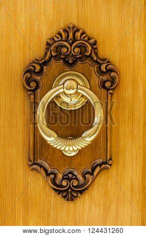 Authentic modern Spanish Brass Door Knocker. showing heavy brass knocker set in carved pine on a front door