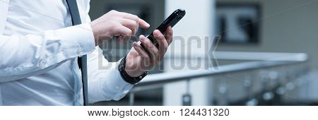 Close-up of elegant businessman picking up the number on his cell phone. Calling to important client