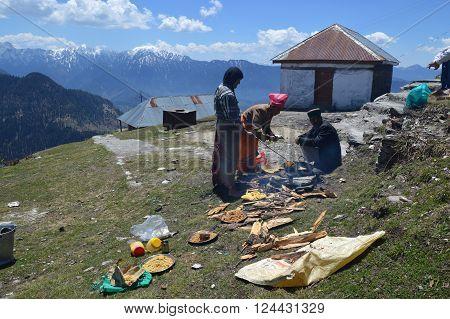 Shimla-Apr 24: Men preparing halwa poori(puri) outdoors on hillside during tonsure(mundan) ceremony at Shrai Koti Mata temple, Shimla Apr 24, 2014 in Himachal Pradesh, India, Asia.