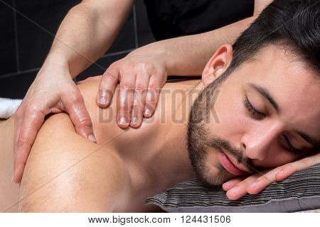 Close up of physiotherapist dong healing shoulder massage on young man.