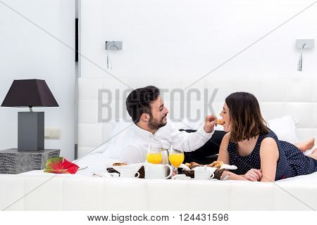 Close up portrait of young couple having breakfast in hotel suite.